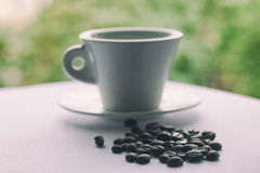 Coffee beans and a cup on the table on a background of green pla Royalty Free Stock Photo