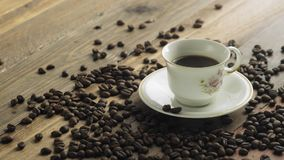 Coffee beans and cup of coffee on table. 4K stock video footage