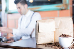 Coffee beans in cup and two paper bags Stock Image