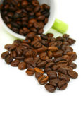 Coffee beans cup on white background. Coffee beans spilled out of green cup,  isolated on white background (shallow depth of field Stock Images