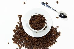Coffee Beans In Cup. A white coffee cup full of coffee beans spilling out on a white background royalty free stock photo