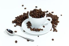 Coffee Beans In Cup. A white coffee cup full of coffee beans spilling out on a white background stock photos