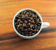 Coffee beans in a cup. Whole coffee beans in a cup on a wooden background Royalty Free Stock Photography