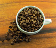 Coffee beans in a cup. Whole coffee beans in a cup on a wooden background Stock Photos