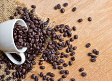 Coffee beans and cup on wood background Royalty Free Stock Images