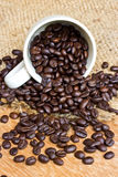 Coffee beans and cup on wood background Royalty Free Stock Image