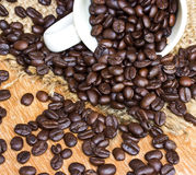 Coffee beans and cup on wood background Royalty Free Stock Photography