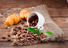 Coffee beans in cup on wood texture Royalty Free Stock Image