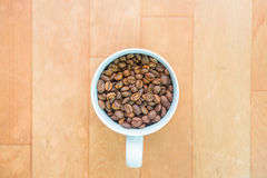 Coffee beans in a cup. On wooden floor stock photography