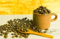 Coffee beans and cup on the wooden table.  Royalty Free Stock Images