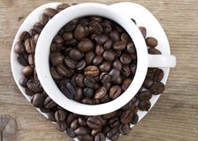 Coffee beans in a cup on the wooden table Royalty Free Stock Photos