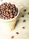 Coffee beans in a cup on a wooden table. Selective focus Stock Image
