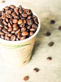 Coffee beans in a cup on a wooden table, selective focus. Image with copy space Royalty Free Stock Image