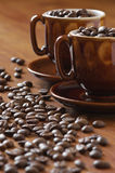 Coffee beans and cups Stock Images