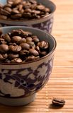 Coffee beans in the cups. Close-up of coffee beans in the painted cups stock images