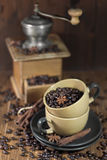 Coffee beans in the cups and old coffee mill. Roasted coffee beans with star anise and cinamon in the ceramic coffee mugs with old coffee mill. Selective focus Royalty Free Stock Images