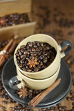 Coffee beans in the cups. Roasted coffee beans with star anise and cinamon in the ceramic coffee mugs/ Selective focus Stock Photo