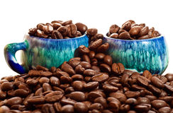 Coffee beans and cups on a white background Royalty Free Stock Images
