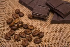 Coffee beans and dark chocolate on a linen napkin. stock images