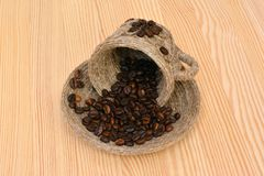 Coffee beans in a decorative cup and saucer on the wooden table. stock images