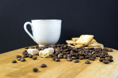 Coffee beans on a desk. Coffee beans, biscuits, sugar and white cup on a wooden desk stock photography
