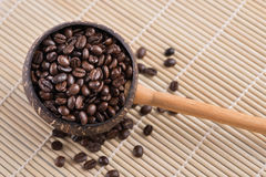 Coffee beans in dipper. On wood background Stock Photography