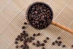 Coffee beans in dipper. On wood background Royalty Free Stock Images