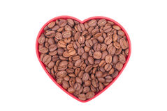 Coffee beans in a dish in the shape of a heart. Stock Image