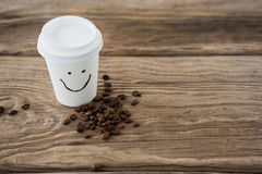 Coffee beans and disposable coffee cup with smiley face Royalty Free Stock Photo