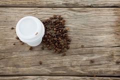 Coffee beans with disposable coffee cup Stock Images