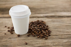Coffee beans with disposable coffee cup Royalty Free Stock Photo