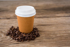 Coffee beans with disposable coffee cup on wooden table Stock Images