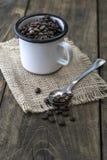 Coffee beans in an enamel mug. Stock Photos