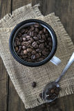 Coffee beans in an enamel mug. Stock Images