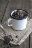 Coffee beans in an enamel mug. Royalty Free Stock Images