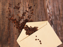 Coffee beans in envelope on wooden background Stock Photography