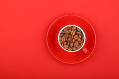 Coffee beans in espresso cup with saucer on red Royalty Free Stock Images
