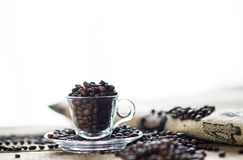 Coffee beans in espresso cup. On wooden texture with coffee bag royalty free stock photography