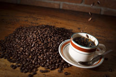 Coffee beans are falling into a black coffee cup Stock Photography