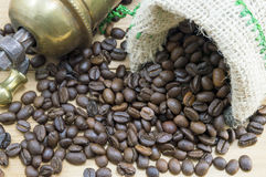 Coffee beans falling from coffee bag next to a vintage coffee gr Stock Image