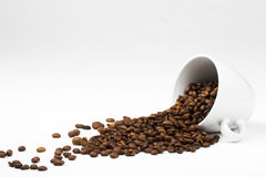 Coffee beans falling from a coffee cup. Some coffee beans falling from a coffee cup on white background royalty free stock photography