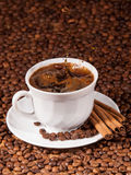 Coffee beans falling into a cup of coffee Stock Images