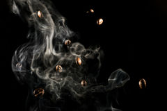 Coffee beans falling down trough smoke over black background - isolated Royalty Free Stock Photo