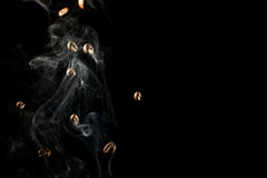 Coffee beans falling down trough smoke over black background - isolated Royalty Free Stock Images
