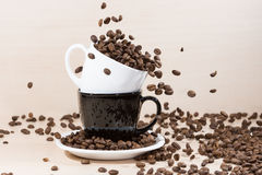 Coffee beans falling down into white cup standing on a black cup on white plate. Stock Photo