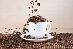 Coffee beans falling down into white cup standing on white plate standing on tablemat. Stock Photography