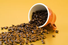 Coffee beans falling from mug. Coffee beans falling from tilted cappuccino cup Royalty Free Stock Photos
