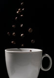 Coffee beans falling in a mug Royalty Free Stock Photography