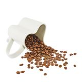 Coffee beans falling out of cup Royalty Free Stock Photo