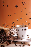 Coffee beans falling on table with coffee cup Stock Photos